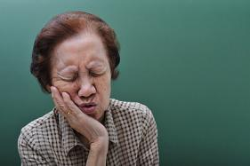 An older woman experiencing pain from her teeth caused by tooth decay.
